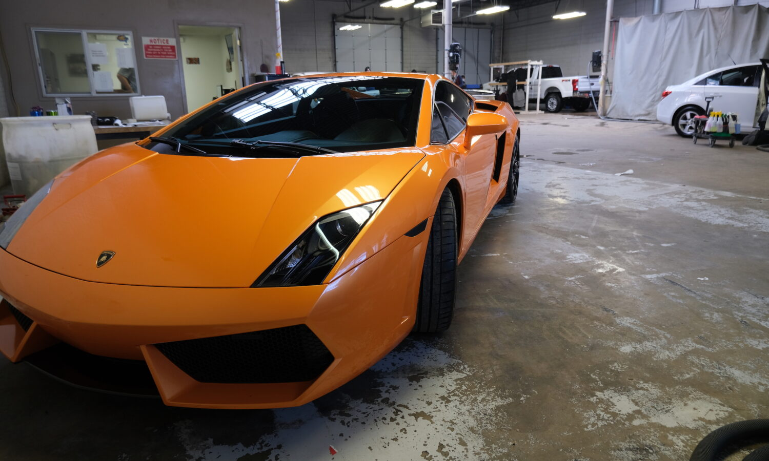 orange Lamborghini sitting inside detail shop