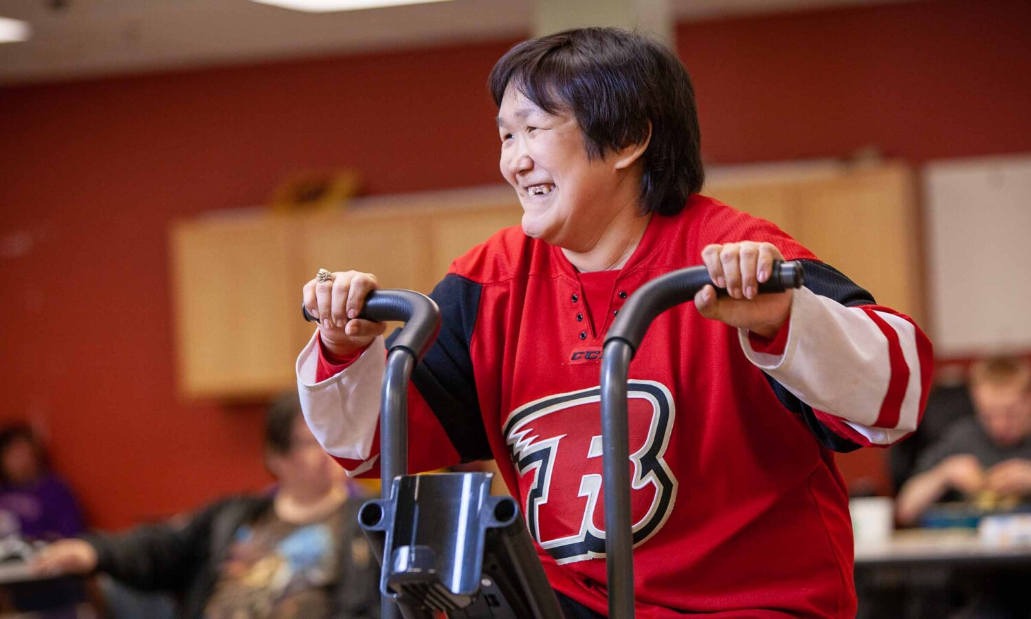 woman smiles while riding stationary bike